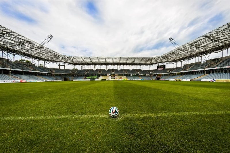 A ball on a pitch on an empty stadium