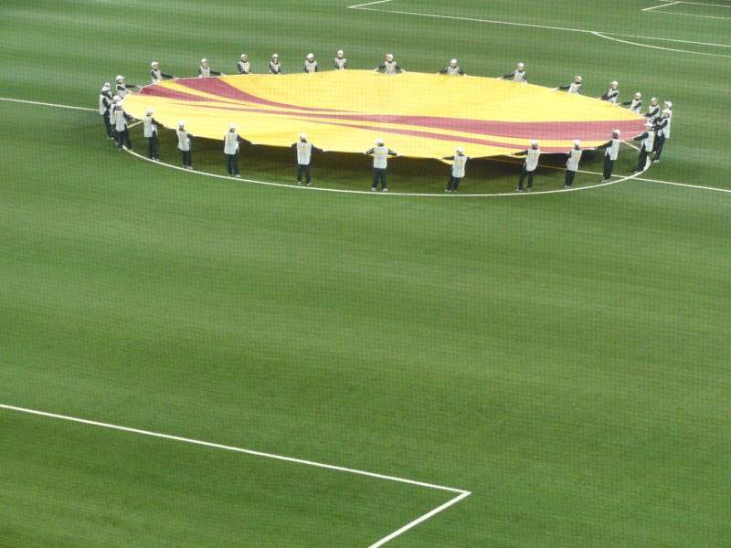 People holding a Europa League logo on the pitch
