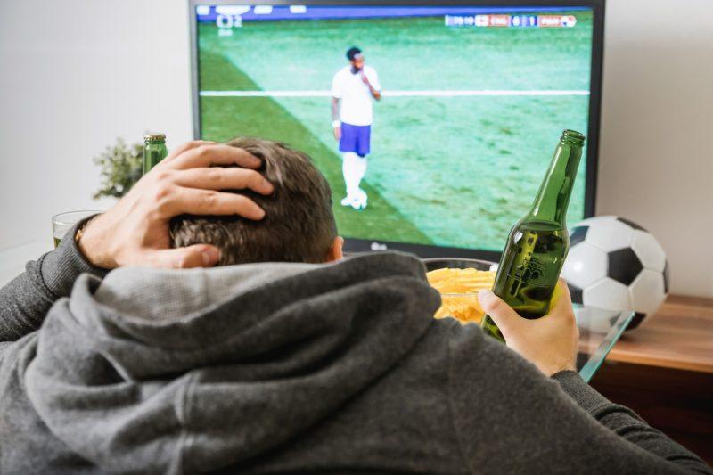 A distraught man watching a soccer match
