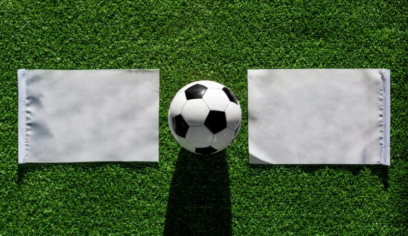 A football between two white flags on grass