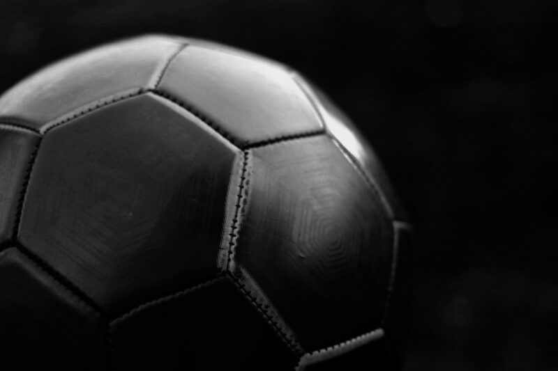 A Black football with a black background